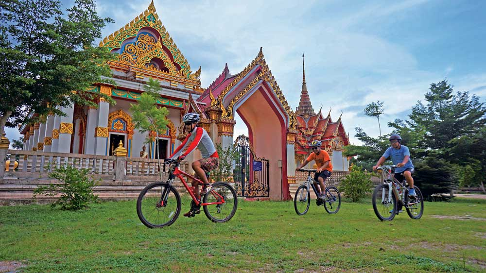 Cycling by a temple in Khao Lak