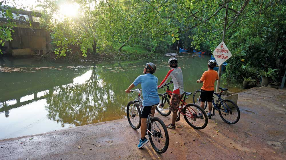 Cyclists by a small lake in Khao lak